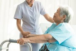 Cheerful asian nurse visiting elderly pa