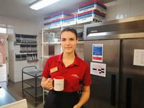 Staff wearing uniform holding 'Ash' mug.