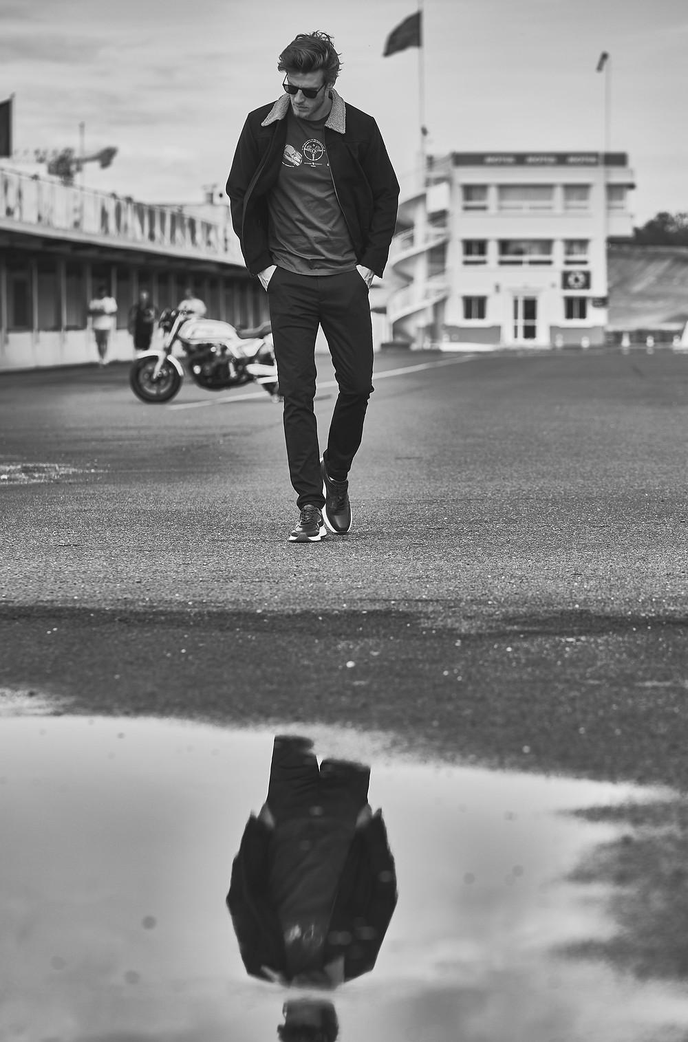 Photo en noir et blanc de mode. Un homme marche sur un circuit de moto. L'homme est habillé d'une veste de marque Benson & Cherry, d'un tshirt sérigraphié de couleurs bleu de la marque Benson & Cherry et d'un pantalon rouge de la marque Benson & Cherry. L'homme porte des lunettes de soleil et a les mains dans les poche. Une flaque d'eau de pluie reflète l'image de l'homme qui marche.  Une moto de course est positionnée derrière lui. Une moto de course est positionnée derrière