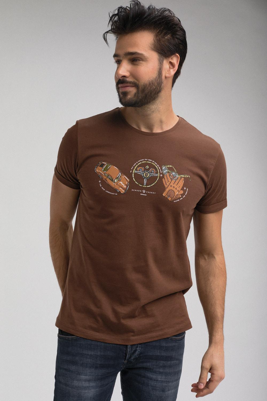Photo de mode masculine Prêt-à porter. Cadre format portrait. Photo couleur. Un homme porte un tee-shirt de couleur marron et un jeans. L'homme est souriant. Le tee-shirt est sérigraphié d'un dessin. Le dessin représante un voiture de la marque Porshe, d'un volant de voiture, d'une paire de gants ainsi qu'une paire de lunettes.