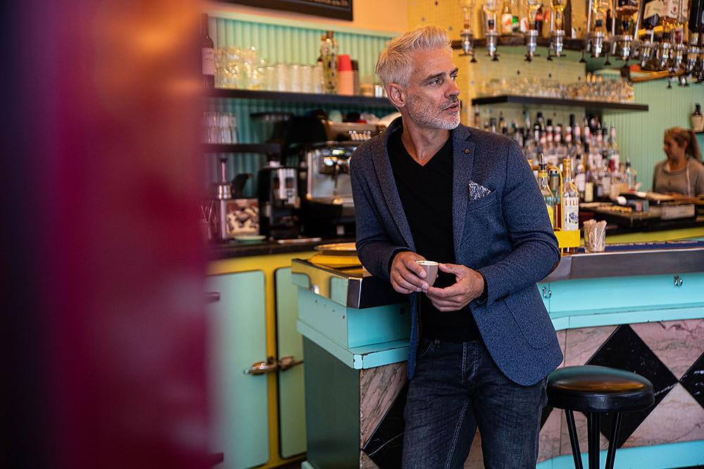 Un homme habillé en Benson & Cherry déguste un café au comptoir d'un café