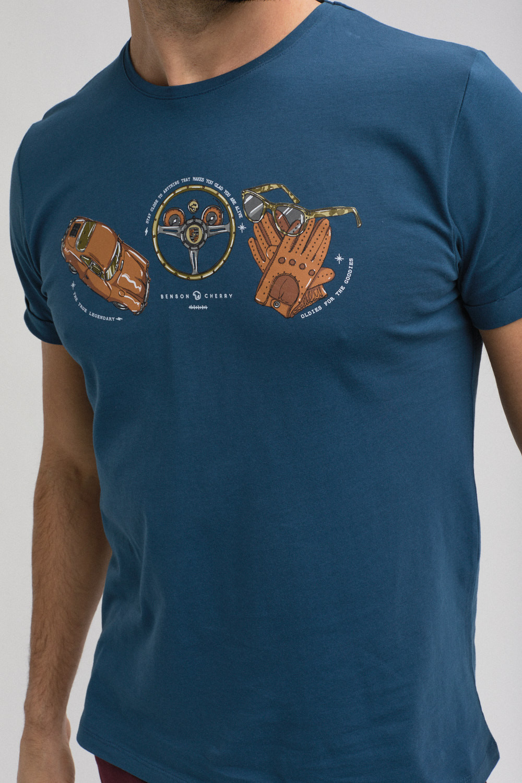 """Photo couleur cadrée en format portrait. Buste d'un homme portant un Tee-Shirt de la marque """"Benson & Cherry"""" de couleur bleu et sérigraphié d'un dessin représentant une voiture, un volant de voiture, une paire de gants ainsi qu'une paire de lunettes."""