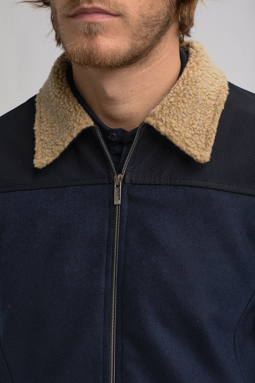 """image couleur bleu. Photo mode masculine prêt-à porter de la marque """"Benson & Cherry """". Gros plan veste bleu marine. col de veste beige en peau de monton."""