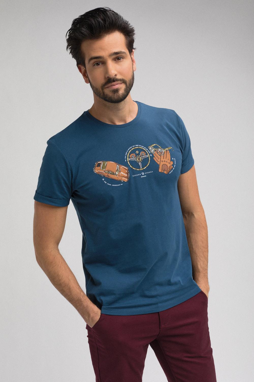 """Photo couleur de mode masuline. Un homme porte un tshirt de la marque """"Benson & Cherry"""" de couleur bleu avec une sérigraphie représentant une voiture, un volant, une paire de gants ainsi qu'une paire de lunette. L'homme sur la photo est de face et a un regard franc et souriant. La photo est cadrée en format portrait."""