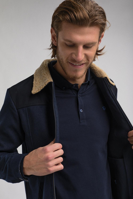 """image couleur format portrait. Photo mode masculine prêt-à porter de la marque """" Benson & Cherry """". Homme souriant. Photo homme portrait et buste. L'homme porte une veste bleu marine à col beige."""