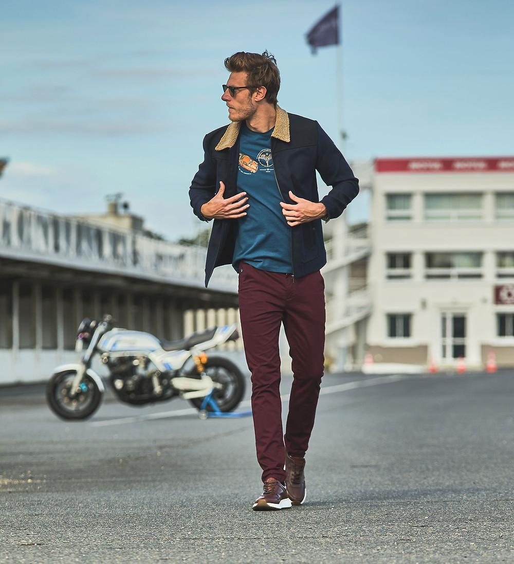 Photo en couleur de mode pret à porter masculin. Un homme marche sur un circuit de moto. L'homme est habillé d'une veste de marque Benson & Cherry, d'un tshirt sérigraphié de couleurs bleu de la marque Benson &Cherry et d'un pantalon rouge de la marque Benson & Cherry. L'homme porte des lunettes de soleil et a les mains dans les poche. Une moto de course est positionnée derrière lui. Une moto de course est positionnée derrière