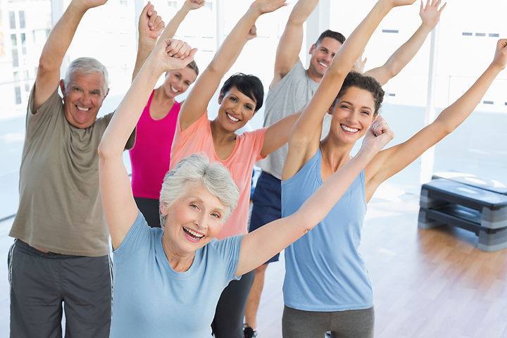 Portrait of smiling people doing power fitness exercise at yoga class in fitness studio.jpg
