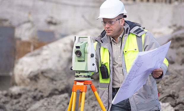 Surveyor at at construction site is insp