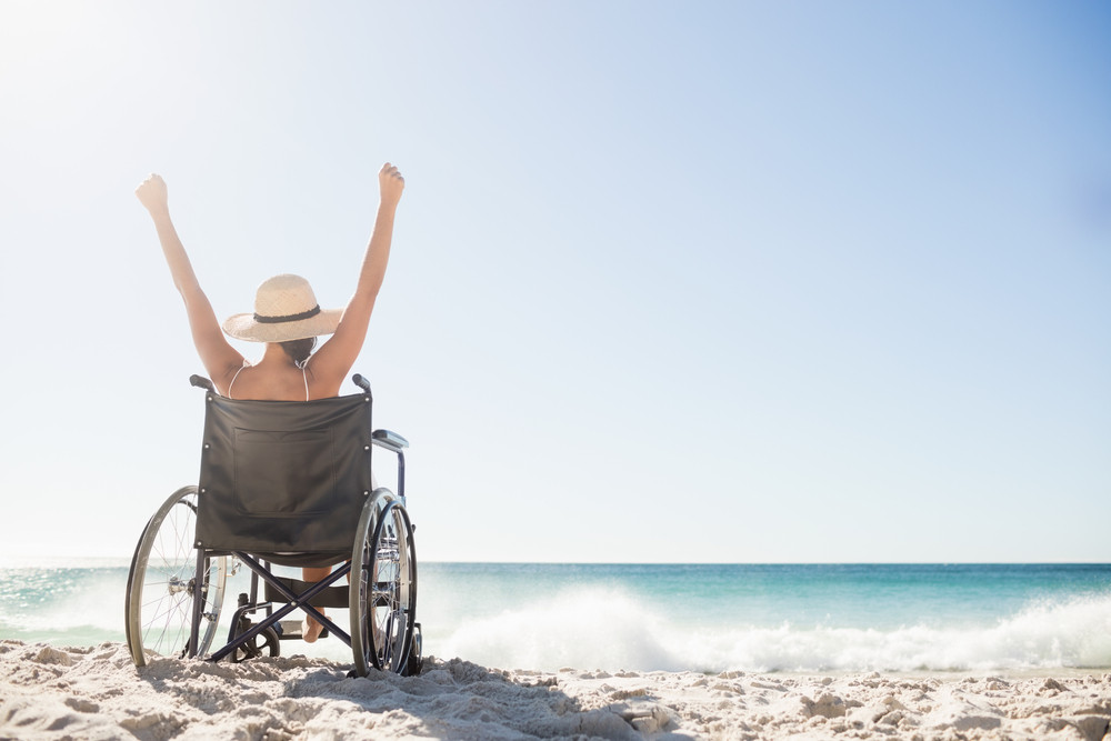 person in wheelchair at beach cheering