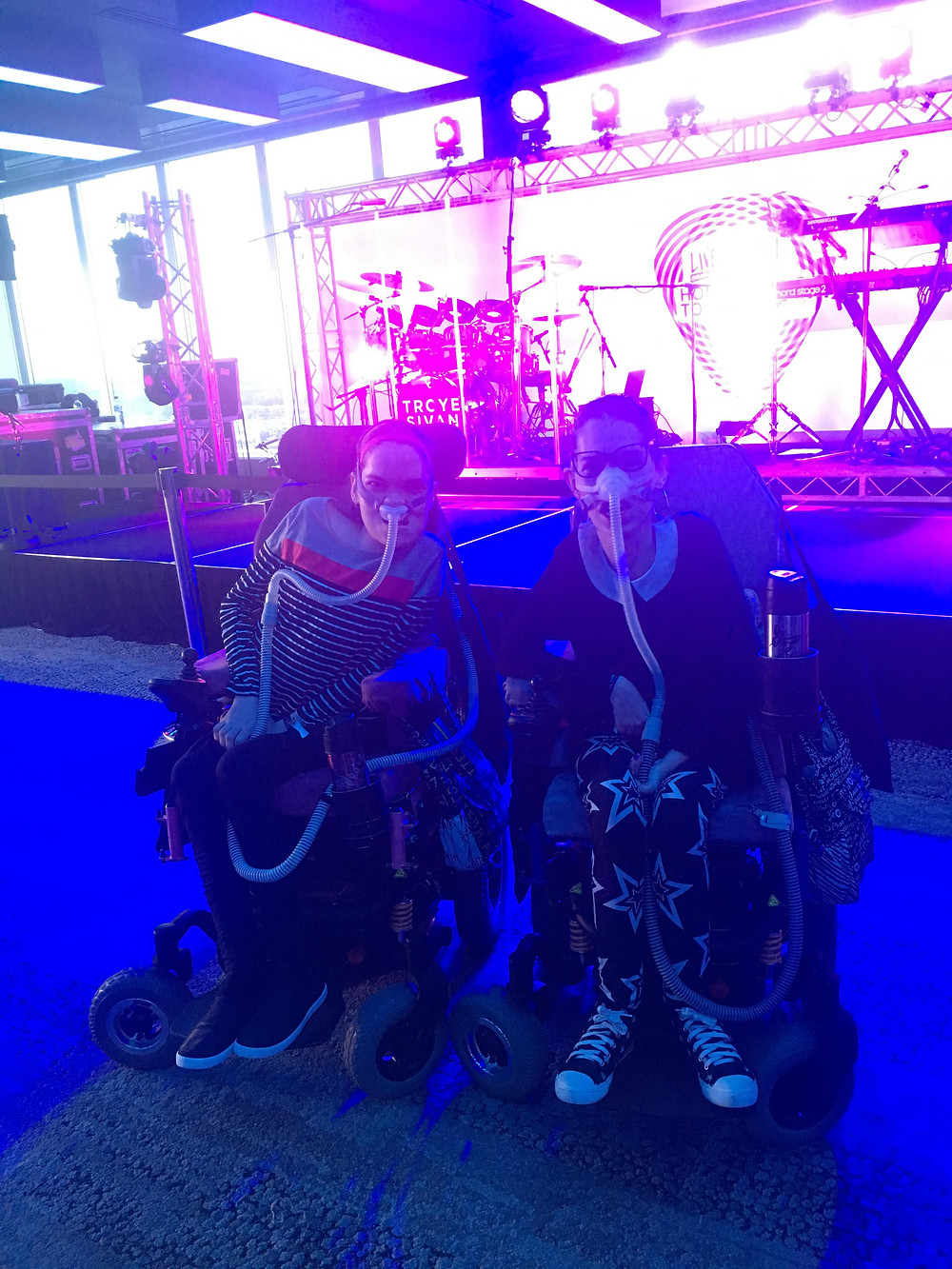 two young women in wheelchairs at a concert