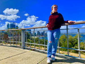 Layne is wearing blue glasses, red stylish jumper, bright blue jeans and white sneakers. She is looking to her left as behind her is a view of Elizabeth Quay, the city. she is leaning on a fence behind her while she is posing for this picture.