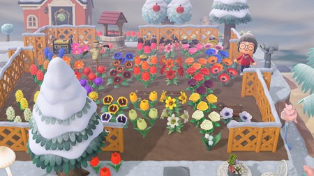 Screenshot  from the game Animal Crossing, showing a character smiling amongst a garden with many different flowers and colours, surrounded by a brown lattice fence. in the background there are snow covered trees, a brick well, binoculars looking over a cliff, and a villager's house.