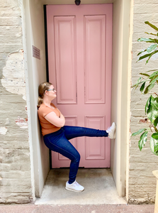 Layne is standing on one leg, while her other leg is up against the wall that she is steering at. she is wearing dark blue high waisted jeans, an orange te-shirt and blue glasses. behind her is a pink door. outside of the mini hallway is a green plant, light grey bricks (they are old) and two floors one is light grey and the other one is bright pink.
