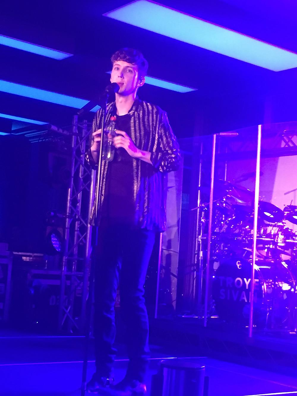 Troye Sivan on stage singing
