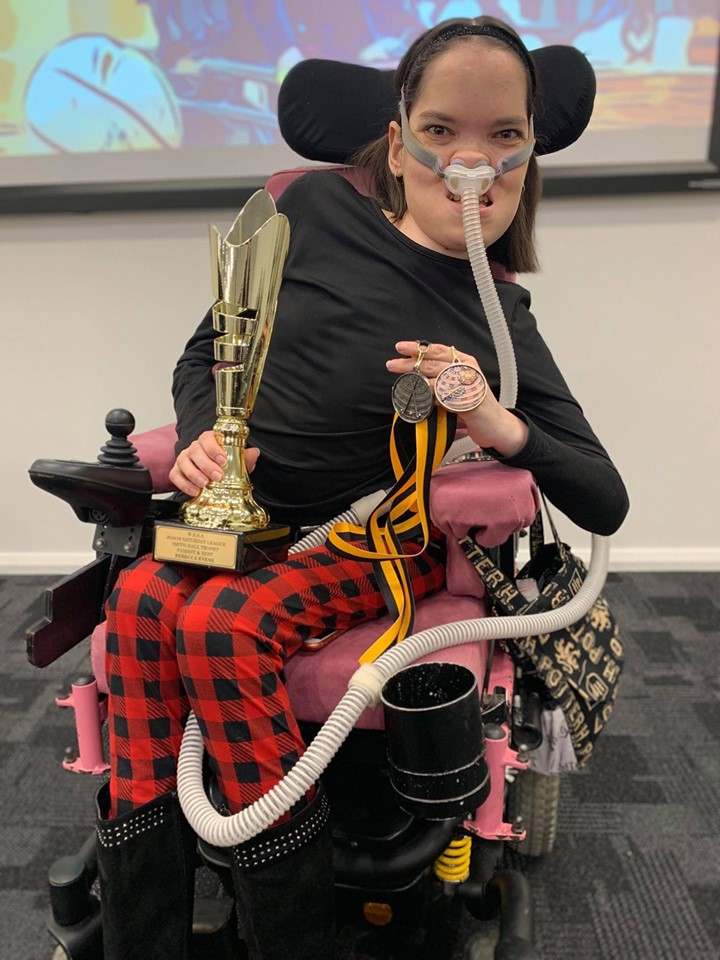 Young woman in wheelchair with trophy and medals