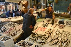Foto de um mercado de peixe. Há várias bancadas com diferentes tipos de peixes expostos, um vendedor e um possível comprador. No fundo da imagem, há outros tipos de mercado.