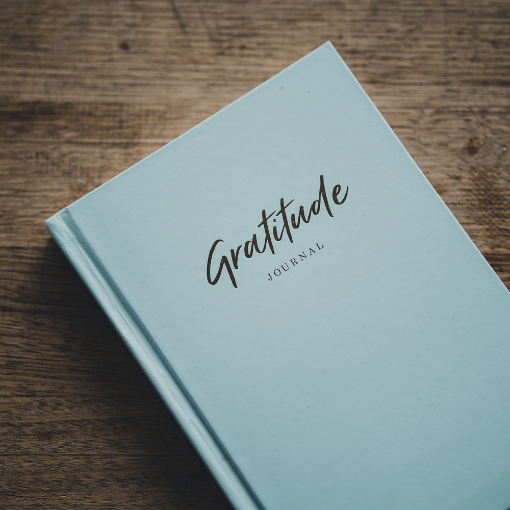 """Photo of a grey blue book, entitled """"Gratitude Journal"""""""