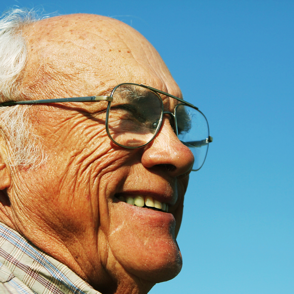Photo of a smiling elderly white man, wearing glasses. The sky is blue and he's bathed in sunshine.