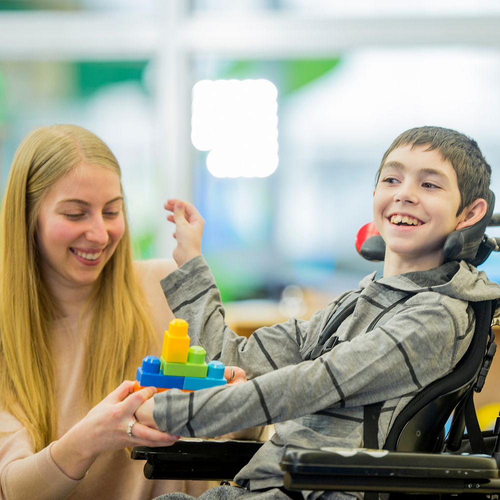 Photo or a child with cerebral palsy playing, smiling and playing with lego with his Mum