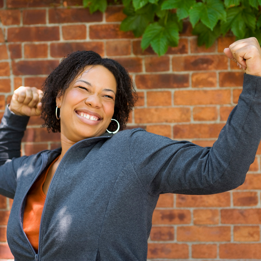 Photo of a black lady, smiling and with her arms in the 'I am strong' position.
