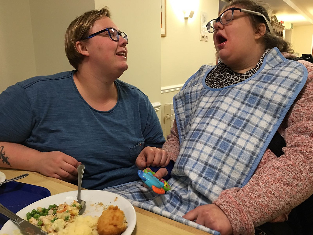 Photo of a young lady with complex needs, eating her dinner, supported by her sister