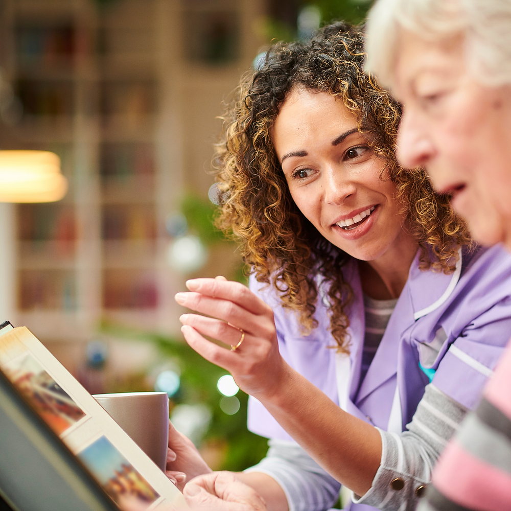 A photo of a female carer, chatting and having a cup of tea with an elderly lady. They are looking at a photo album and smiling.