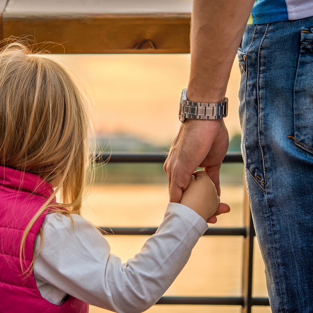 A photo of a Dad holding his daughter's hand. Their backs are to the camera.