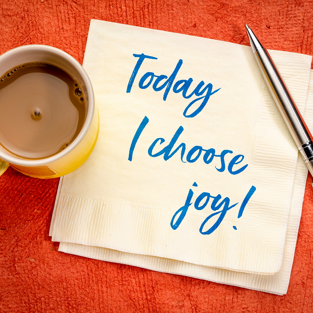 """Aerial photo of a cup of tea and a napkin on an orange towel. With the words """"Today I choose joy"""" written in blue ink, on the napkin."""