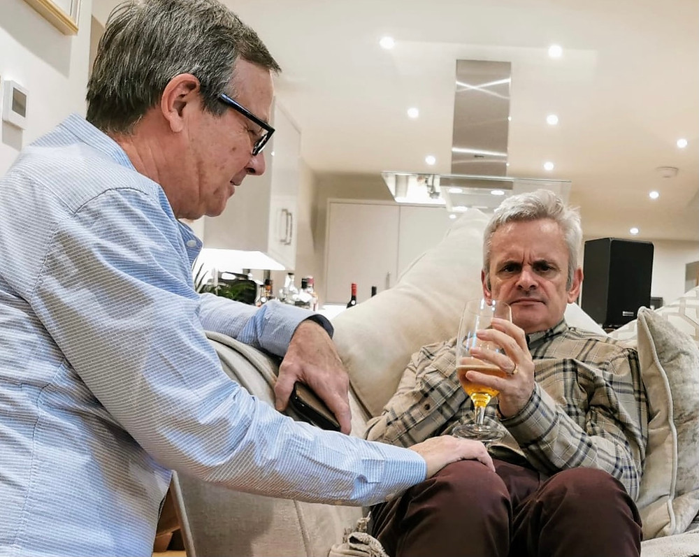 A photo of Mike caring for his husband Tom, who has dementia. Mike is supporting Tom to drink a beer. They are sat in their kitchen.