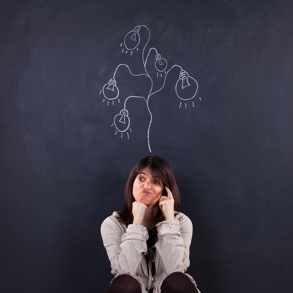 A lady is sitting with her back against a chalkboard. She looks confused and in white chalk there are lots of light bulbs drawn, coming out of her head. Indicating she has lots of ideas.