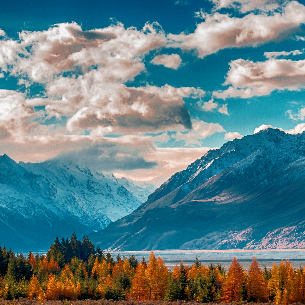Photo of a mountain, with autumnal forest and river below. Bright blue sky with white clouds.