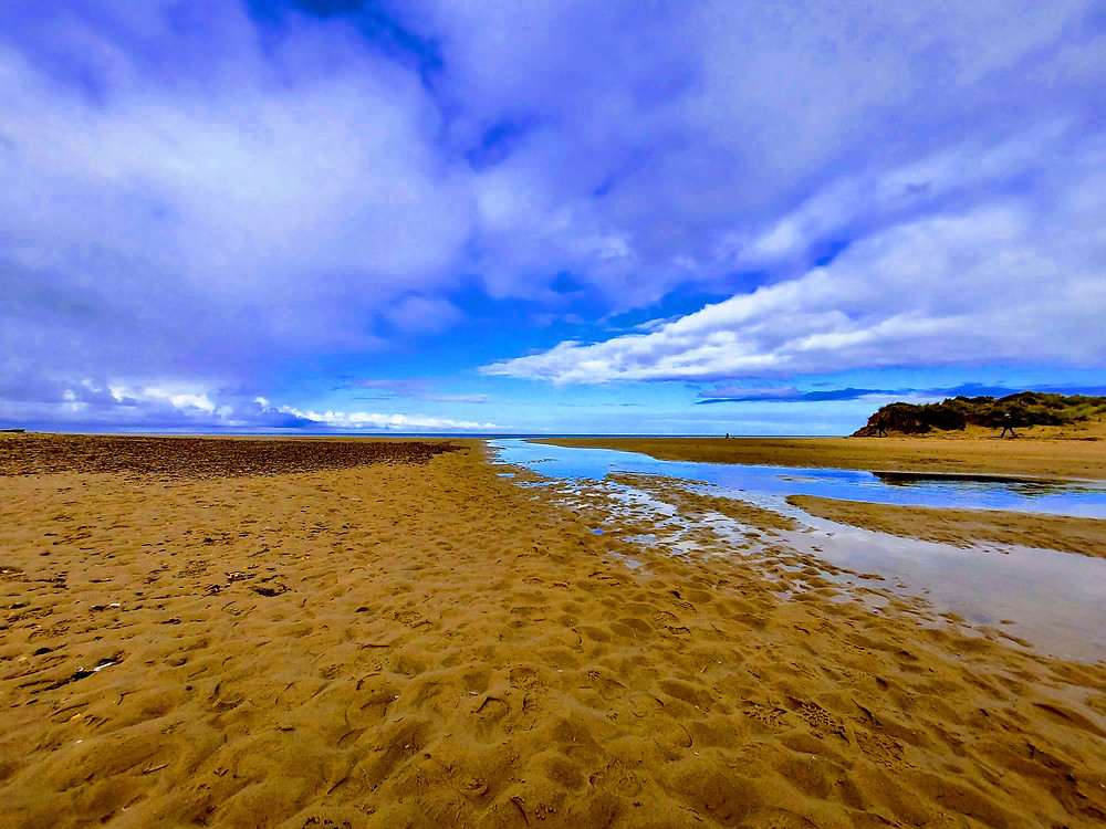 Photograph of Holkham beach in Norfolk, showing an expanse of sand, a blue stream running from the beach to the sea in the far distance. There is a big, bright blue sky with wispy white clouds.