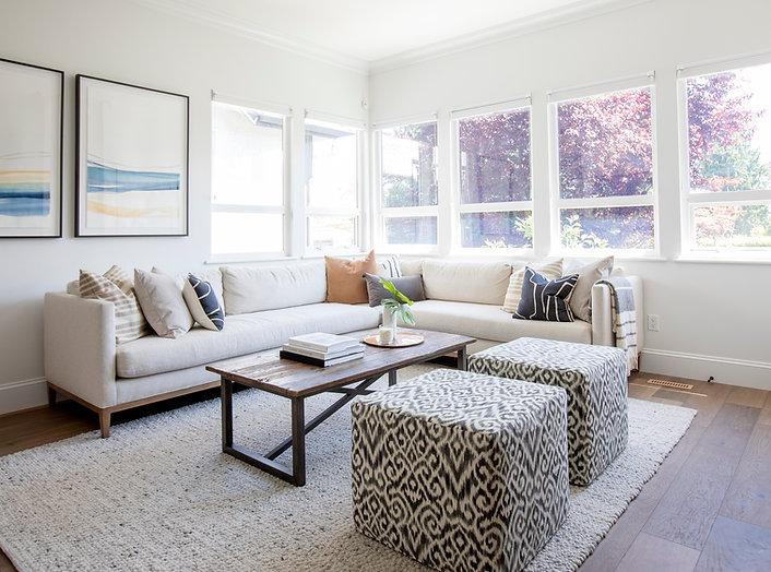 Image of livingroom with cream couch, colorful throw pillows, dark wood coffee table, and two patterned ottomans.