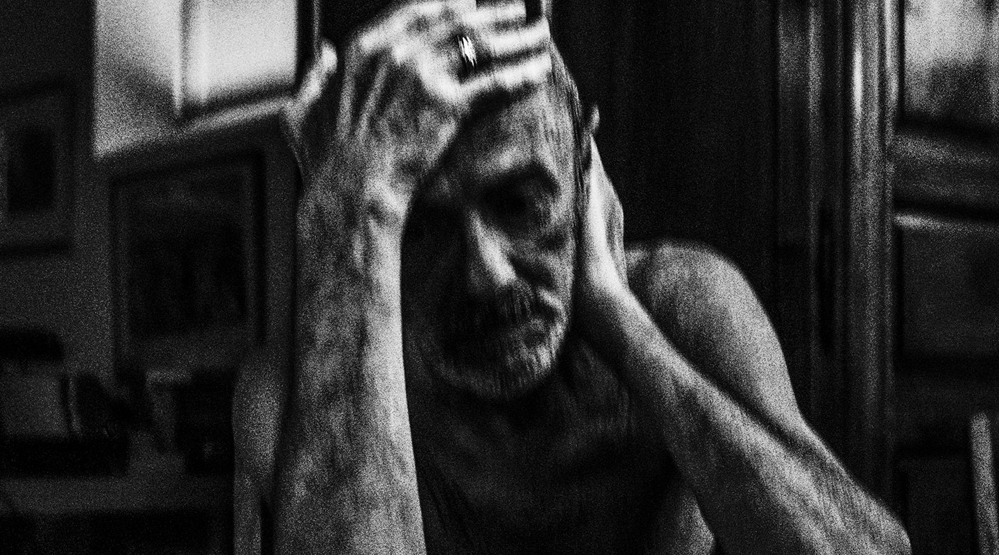 Older man sitting at table, holding his head, in a state of contemplation.