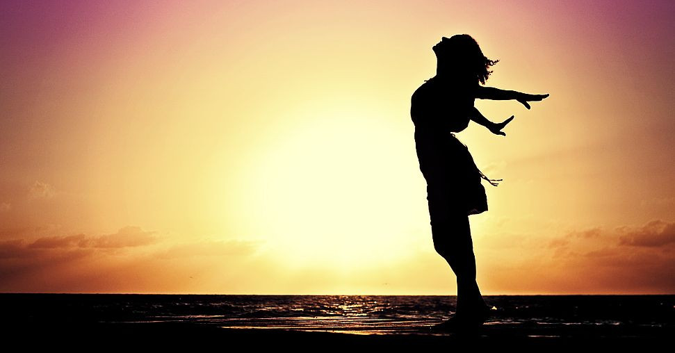 Silhouette of a woman on a beach enjoying the breeze