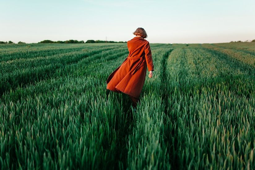 Woman with a red coat walking trough a green field