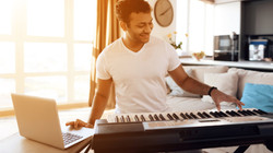 Man playing keyboards at home through virtual lesson