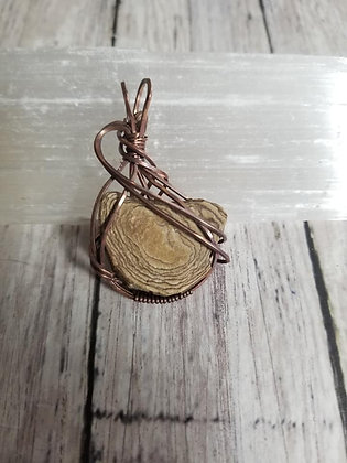 Stone wrapped in oxidized copper wire