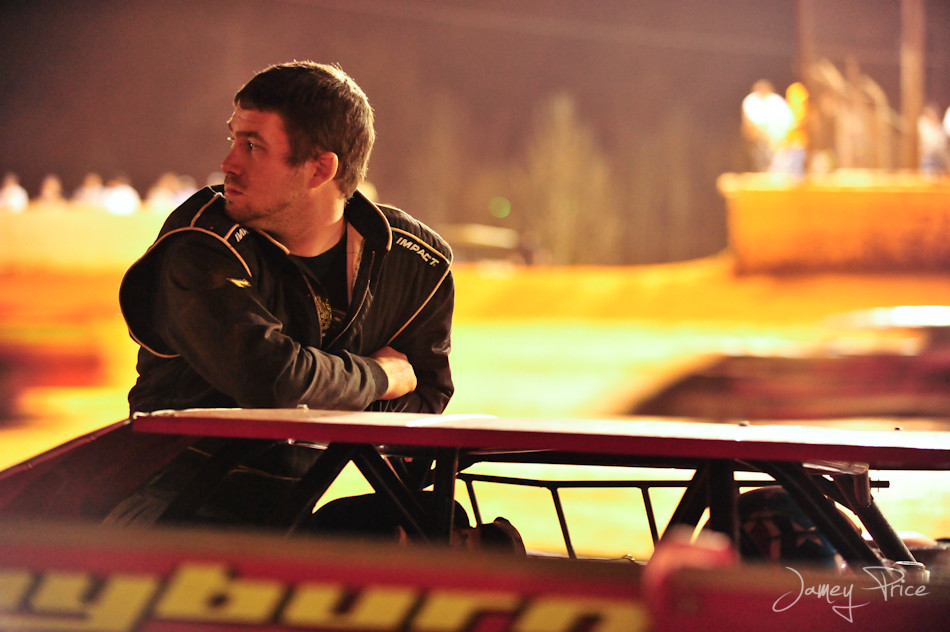 A driver watches racing action after his car broke down early in the race.