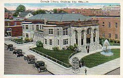 Birdseye view of Oklahoma City Carnegie library, showing a fountain, and Brass Age cars.