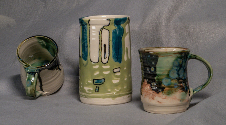 Thrown cups and cylinder with low fire glazes and final high fire glaze and outlining for contrast