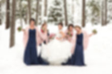 Bride and bridesmaids striking a pose with lots of snow