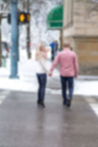 Bride-to-be crossing the street with her fiancé
