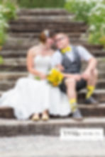 Bride and groom sitting on steps with their foreheads together