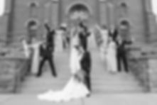 Bridal party celebrating on the steps to a church behind the bride and groom while they kiss