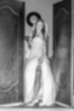 Bride standing in a doorway holding up her wedding dress to show her garter