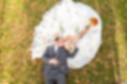 A wedding photo taken from directly above the bride and groom while they are lying on the ground with their faces together and feet in opposite direction