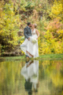Beautiful fall colors surrounding a bride and groom while they kiss, showing their reflection in a pond