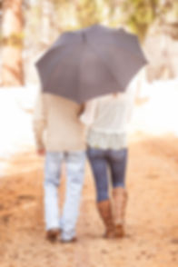 Engaged couple walking away down a path under an umbrella