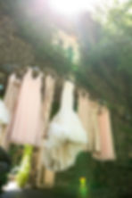 Bride and bridesmaid's dresses hanging on a rock ledge